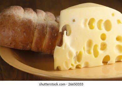 Piece of cheese and bun close-up on yellow plate.