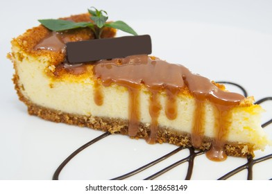 a piece of cheese cake decorated with mint on a white background
