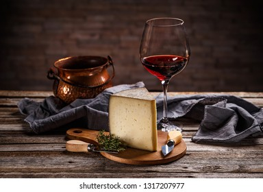 Piece of cheese with glass of red wine on vintage wooden background