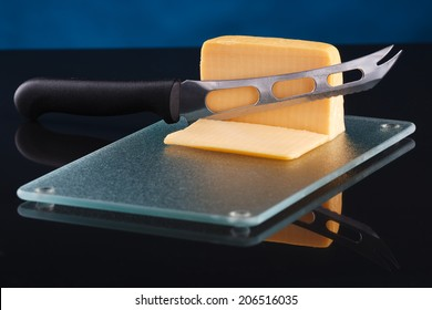 a piece of cheese on a glass cutting board with a knife