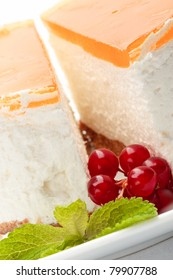 A piece of cheesecake on a plate decorated with red currant and mint