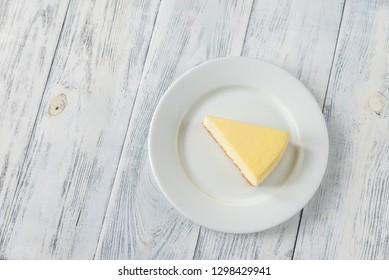Piece of cheesecake on the white plate flat lay