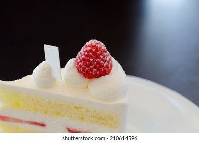 Piece of cheesecake  with strawberry on white plate.