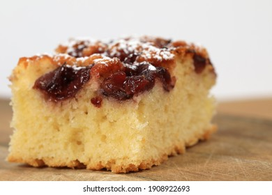 A piece of cherry pie was placed on the surface of the plank with fruit and caster sugar on top.