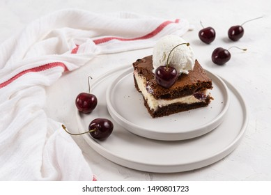 A piece of chocolate brownie with cream cheese, cherry and ice cream ball on the top on white background, homemade bakery and dessert. Bakery, confectionery concept. Copy space, side view