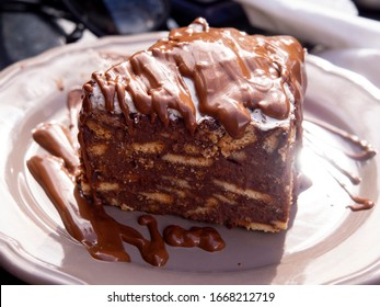 A piece chocolate cake from cookies, poured with chocolate, on a plate in a coffee shop in popular confectionery cafe 1743 in a tourist mountain village Steni, Evia Island, Greece