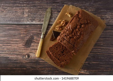 Piece of chocolate cake, fudge or pound cake. Wooden board. Copy space.