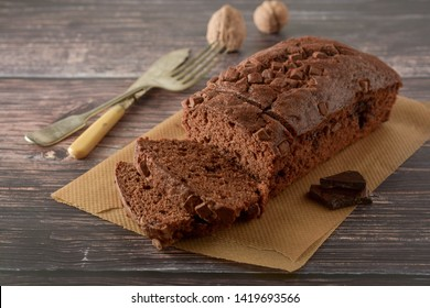 Piece of chocolate cake, fudge or pound cake. Wooden board.
