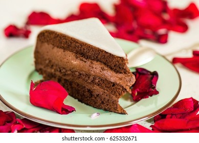 The piece of chocolate cake with marzipan on green plate, sprinkled with red rose petals, on white background