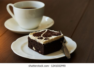 A piece of chocolate cake on wooden table. A cup of coffeee on background