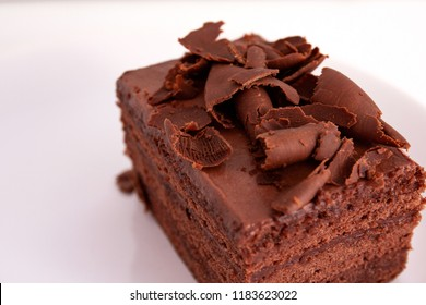 A piece of chocolate cake with shavings on a plate on a white background