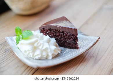 The piece of chocolate cake and whip cream topping with peppermint leaf on the wooden table