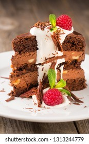 A piece of chocolate cream with cream and raspberries