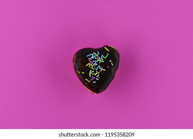 A piece of chocolate dessert on a pink background, decorated with colored sugar.