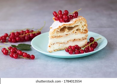 A piece of choux pastry with cheese cream, garnished with red currants. Karpatka cake. Soft focus.