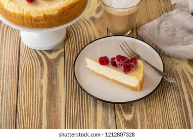 Piece of classic cheesecake with raspberries and coffee on a wooden background. Copy space.