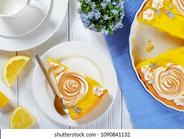 piece of Classic french lemon tart or Tarte au citron on a plate and in a baking dish with a custard lemon filling decorated with meringue roses and edible fresh flowers, view from above, close-up