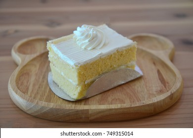 A piece of coconut cake on cute wooden plate
