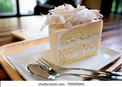 A piece of coconut cake on white plate.