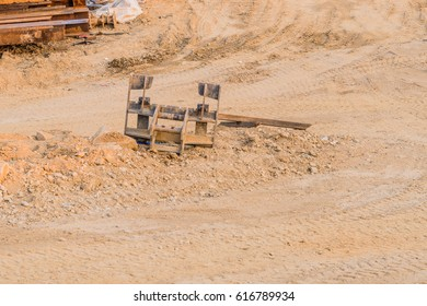 Piece of construction equipment laying on the ground at construction site with pile of metal beams in left top frame