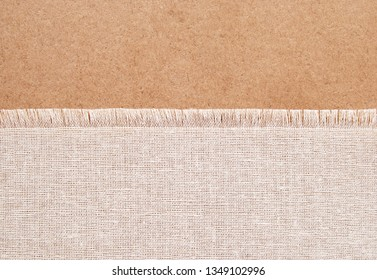 A piece of cotton fabric with fringe on rustic brown background for text or banner