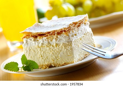 Piece of cream and custard pastry with melissa and grapes