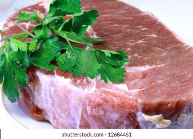Piece of crude meat with leaves of a parsley