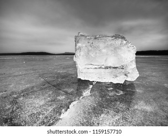 Piece of crushed ice on dark natural  background. Authentic texture of a black and white ice laying on dark floe
