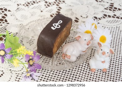 """Piece of delicious chocolate cake """"Note""""on a crystal vase with flowers and decorative pig."""