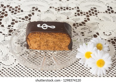 """Piece of delicious chocolate cake """"Note""""on a crystal vase with flowers."""