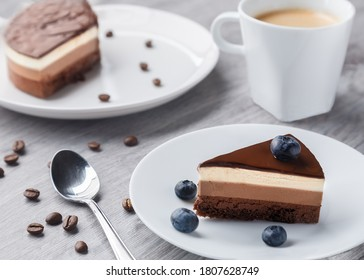 Piece of delicious chocolate cake with triple different colour types of souffle in soft focus. Tiramisu style with white and brown color.