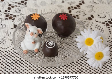 Piece of delicious chocolate round cakes on a crystal vase with flowers and decorative pig.