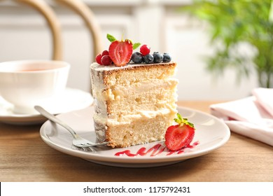 Piece of delicious homemade cake with fresh berries served on wooden table