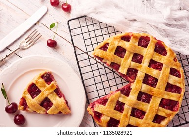 Piece of Delicious Homemade Cherry Pie with a Flaky Crust on rustic wooden white background