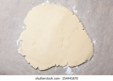 A piece of dough, rolled out and flat, ready to make cookies.