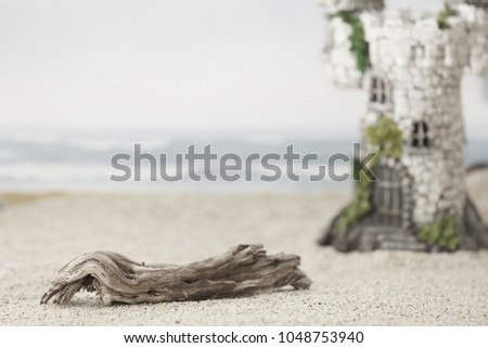 A piece of driftwood on the sand at the beach with a castle and ocean waves in the background.