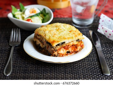 A piece of eggplant lasagna on a white dish with knife, fork, salad, and a glass of iced water.