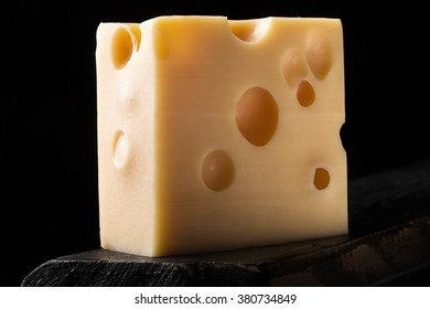Piece of emmental cheese on a wooden surface. Dark background