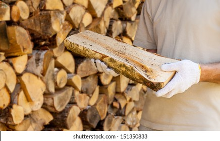 A piece of  firewood in man hands on stacked chopped wood background