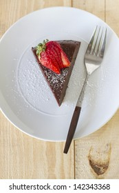 A piece of flourless chocolate cake with powdered sugar.