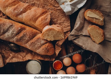 A piece of french baguette with butter on the linen fabric, craft paper and dark wooden background. Wodeen knife and eggs. One glass of milk