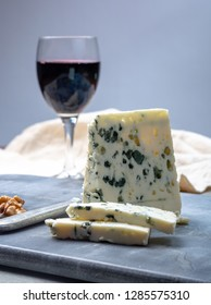 Piece of French blue cheese Roquefort, made from sheep milk in caves of Roquefort-sur-Soulzon and glas with red wine