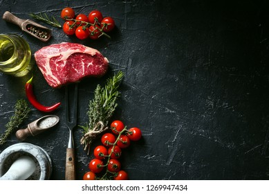 a piece of fresh beef. rib-eye steak. with accompanying ingredients for cooking. concept of delicious dinner.