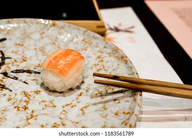 A piece of fresh crab sushi sits atop rice next to chopsticks on a plate, served at a ryokan as part of the kaiseki meal for dinner in Japan.