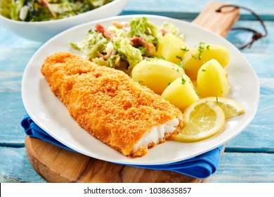 Piece of fresh crispy breaded fish with potatoes served on plate