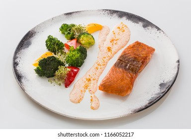 A piece of fried salmon fish with sauce and vegetables in a plate isolated on white background.