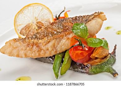 Piece of fried white fish on a cushion of grilled vegetables. Close-up.