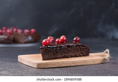 A piece of gluten-free chocolate cake decorated with cranberries on the kitchen board, on a black background. Healthy eating. Copy space