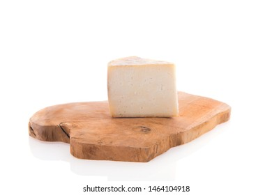 Piece goat cheese on wooden cutting board