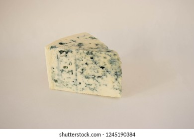 A piece of gorgonzola cheese on a white background